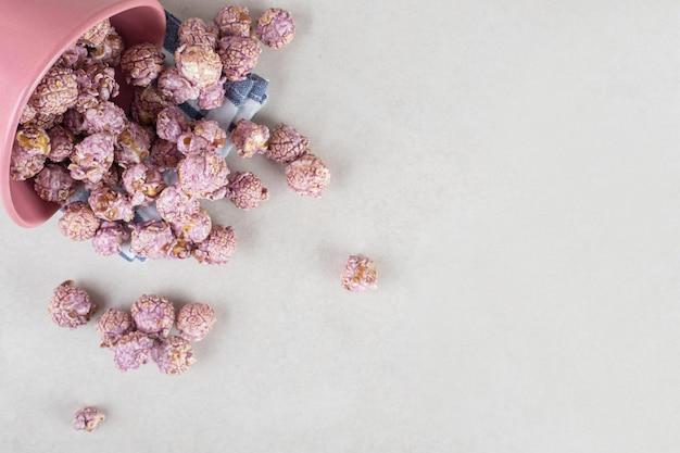 Schüssel voll lila popcorn auf einem gefalteten handtuch auf marmortisch umgefallen.