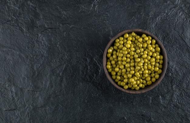 Schüssel voll mit grünen marinierten grünen erbsen auf schwarzem tisch.