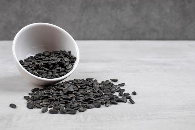 Schüssel voll mit schwarzen sonnenblumenkernen auf stein gelegt.