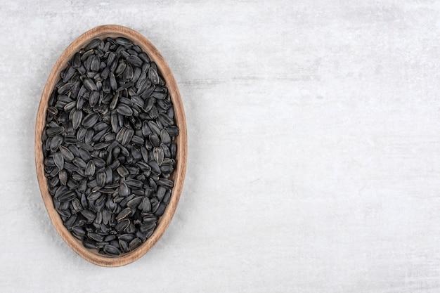 Schüssel voll von schwarzen sonnenblumenkernen, die auf steintisch gelegt werden.