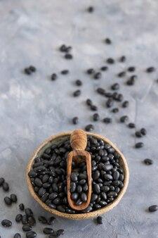 Schüssel voller getrockneter schwarzer bohnen mit einer holzschaufel auf grauem tisch hautnah mit kopierraum. gesundes essen und vegetarisches konzept. traditionelle lateinamerikanische cousine-zutat