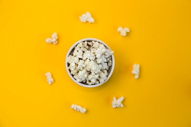 Schüssel voller popcorn auf gelbem hintergrund und popcorn um die schüssel herum. schau dir lustige filme an.