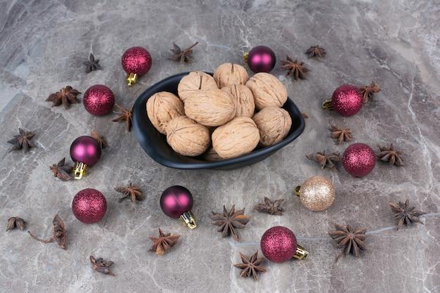 Schüssel walnüsse mit nelken und weihnachtskugeln.