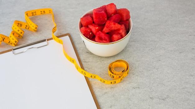 Schüssel wassermelonenfruchtwürfelscheibe mit messendem band und weißbuch auf klemmbrett