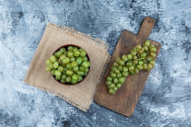 Schüssel weiße trauben auf einem tischset mit weißen trauben auf einem schneidebrett flach lag auf einem dunkelblauen marmorhintergrund