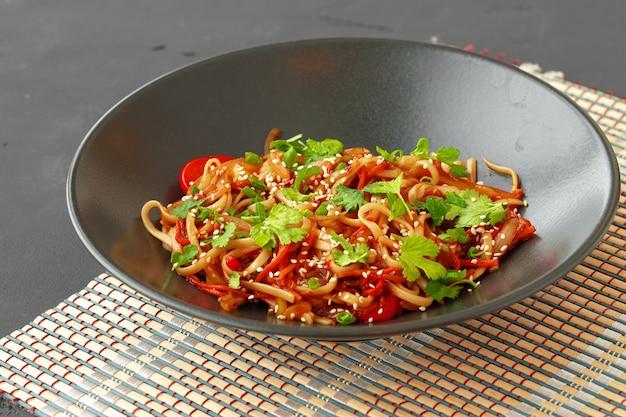 Schüssel wok-nudeln mit gemüse auf schwarzer nahaufnahme