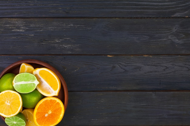Schüssel zitrusfrüchte auf schwarzem hölzernem hintergrund, draufsicht