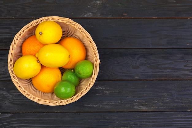 Schüssel zitrusfrüchte auf schwarzer hölzerner, draufsicht