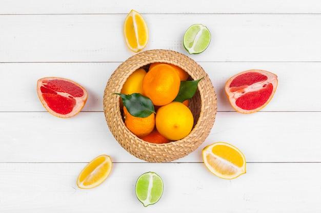 Schüssel zitrusfrüchte auf weißer hölzerner, draufsicht