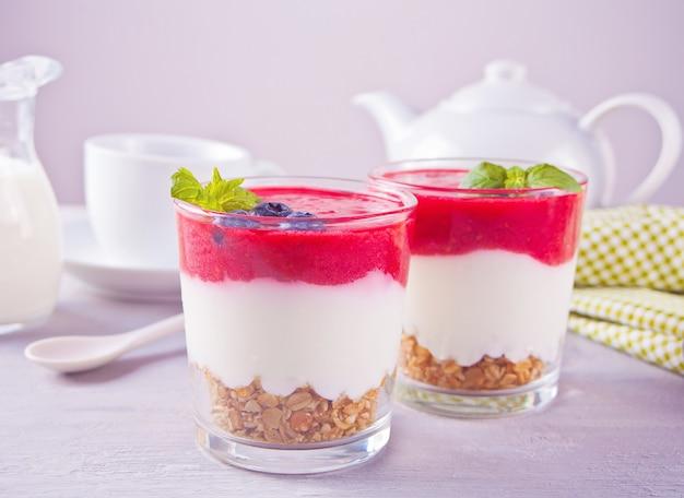 Schüsseln gesundes müsli des frühstücks mit blaubeere, erdbeere und joghurt.