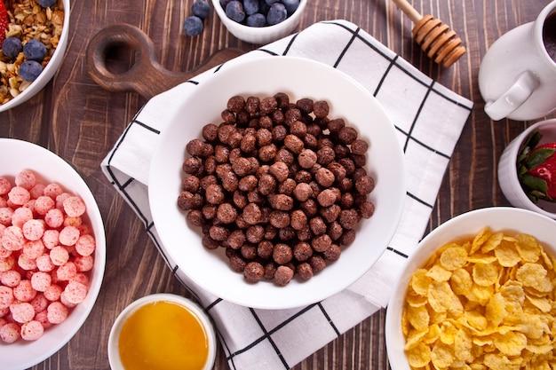 Schüsseln mit erdbeeren, schokoladen-zuckermaisbällchen, müsli und cornflakes mit beeren. leckeres und gesundes frühstücksflocken. draufsicht.
