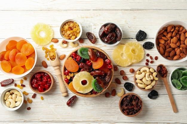 Schüsseln mit getrockneten früchten und nüssen auf weißem holztisch