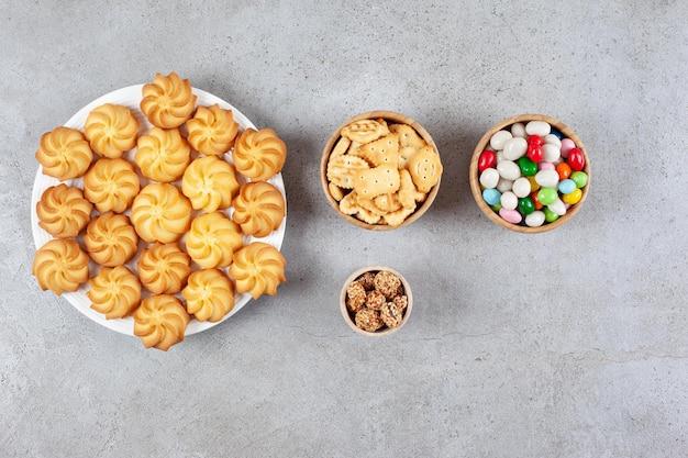 Schüsseln mit glasierten erdnüssen, bonbons und kekschips neben einem teller mit keksen auf marmoroberfläche.