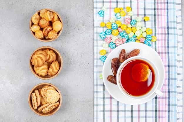 Schüsseln mit keksen und tee mit datteln und bonbons auf marmoroberfläche.