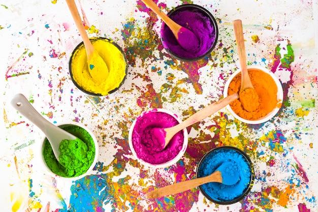 Schüsseln mit löffeln und verschiedenen hellen, trockenen farben