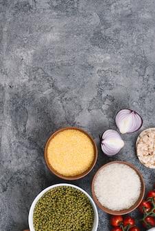 Schüsseln mit reiskörnern; mungobohnen; polenta; zwiebel; kirschtomaten und puffreiskuchen auf konkretem hintergrund