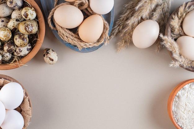 Schüsseln mit rohen hühner- und wachteleiern mit mehl auf beigem tisch.