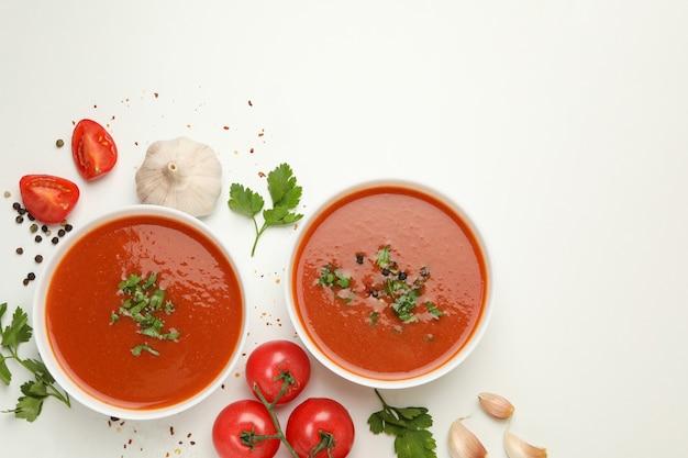 Schüsseln mit tomatensuppe und zutaten auf weiß