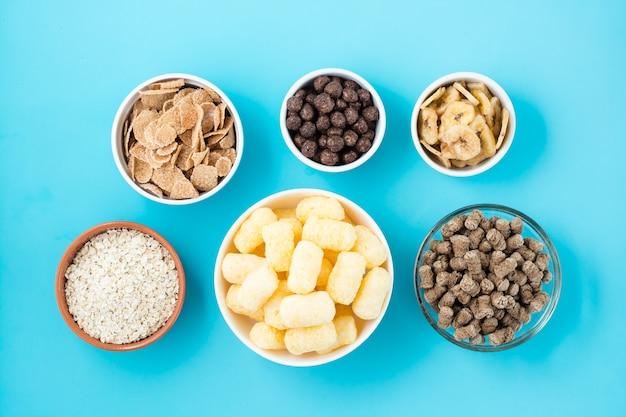 Schüsseln mit verschiedenen arten von frühstück und snacks: haferflocken, maissticks, müsli und kleie auf einem blauen tisch