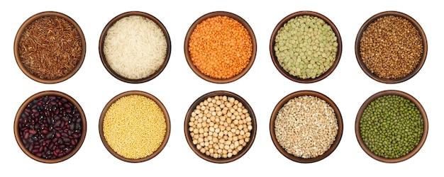 Schüsseln mit verschiedenen getreidesorten und hülsenfrüchten isoliert auf weißem hintergrund