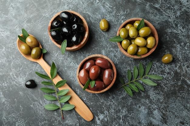 Schüsseln und löffel mit oliven auf schwarzem rauchigem hintergrund