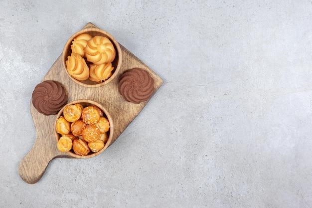 Schüsseln von keksen neben braunen keksen auf holzbrett auf marmorhintergrund. hochwertiges foto