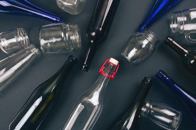 Schütze die umwelt. recycling von leeren bunten glasflaschen auf dunkler draufsicht.