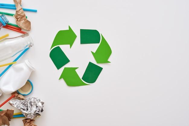 Schütze die umwelt. zerknitterte folie, papier und plastik liegen in der nähe des recyclingsymbols. verschiedene arten von müll unsortiert