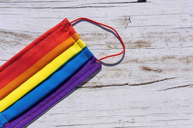 Schützende gesichtsmaske gegen covid-19 mit den farben des regenbogens. lgtb. homosexuell lesben. coronavirus-konzept