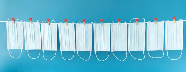 Schützende gesichtsmasken hängen an wäscheklammern mit herzen am seil.