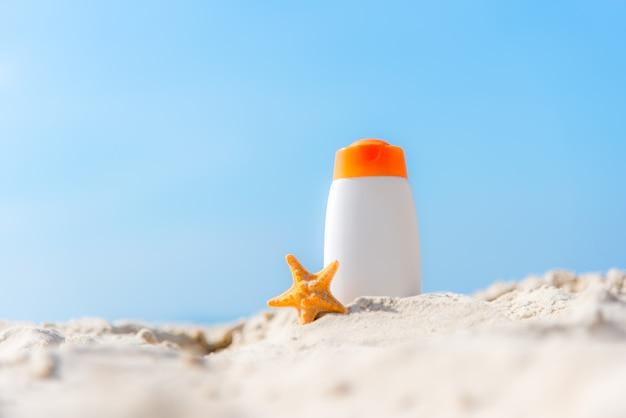 Schützender lichtschutz oder sonnencreme und sonnenbadlotion in den weißen plastikflaschen auf tropischem strand, sommerzubehör im feiertag, kopienraum. sommer-konzept