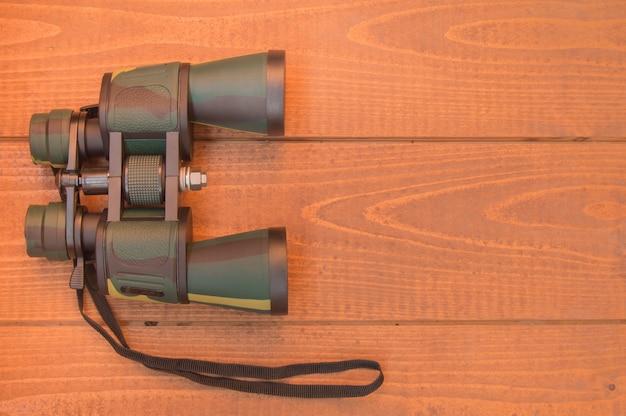 Schützendes kakifarbiges der ferngläser auf hölzernem hintergrund, draufsicht