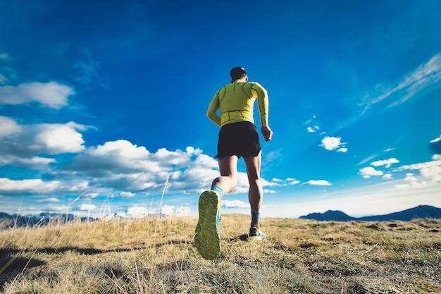 Schuh des läufers in den bergen, die auf wiese trainieren
