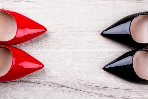 Schuhe auf hölzernem hintergrund. rote und schwarze schuhe. neue warenkollektion. glänzende schuhe für helle frau.