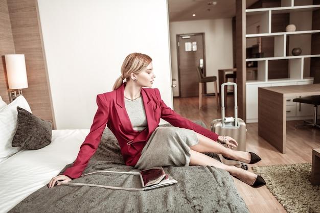 Schuhe ausziehen. müde stilvolle geschäftsfrau, die ihre schuhe nach dem flug auszieht, während sie im hotelzimmer ist