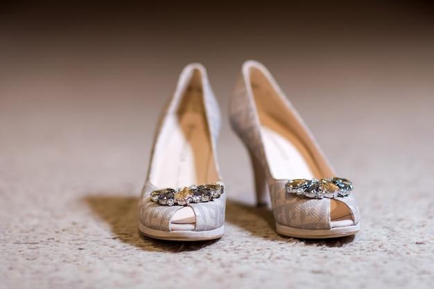 Schuhe der braut mit hohen absätzen auf der hellen oberfläche.