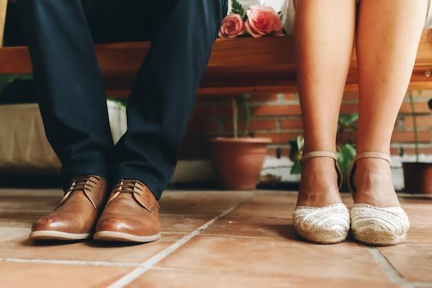 Schuhe des bräutigams und der braut und ihres kleinen hochzeitsstraußes der rosa rosen, die in einer holzbank sitzen und warten. hochzeitstag konzept.