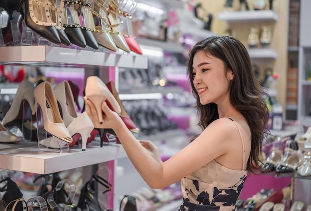 Schuhe des hohen absatzes der jungen frau einkaufs im shop