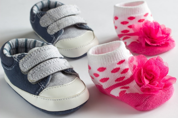 Schuhe für den kleinen jungen und rosa socken für mädchen. weißer hintergrund