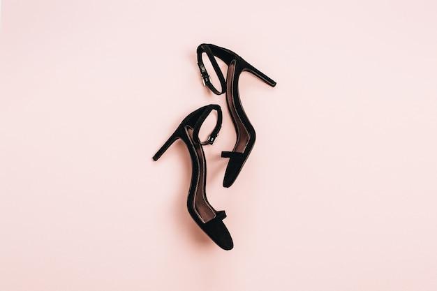Schuhe mit hohen absätzen auf pastellrosa oberfläche