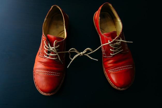 Schuhe mit schnürsenkeln auf schwarzem hintergrund zusammengebunden. schuhe mit haftnotizen bedeckt.