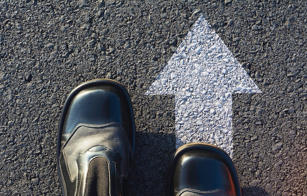 Schuhe stehen an der kreuzung und entscheiden, welchen weg sie einschlagen wollen. möglichkeiten, das konzept zu wählen.