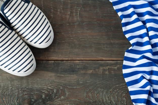 Schuhe und gestreifter stoff auf altem hölzernem hintergrund
