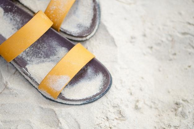 Schuhe wurden auf den sand gelegt. entspannen sie am strand in der nähe des meeres.