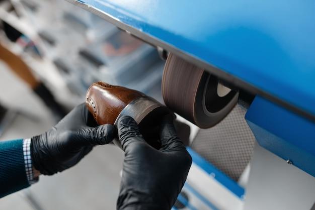 Schuhmacher bearbeitet den schuh auf der schmirgelmaschine, schuhreparatur