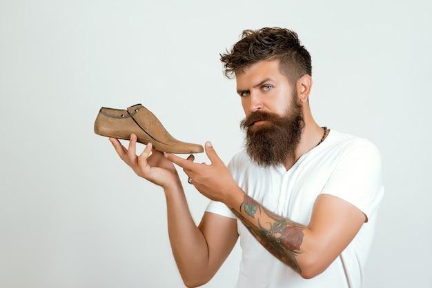 Schuhmacher, der hölzerne schuhe hält