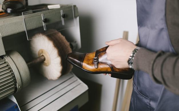 Schuhmacher in der werkstatt, die neue handgemachte schöne lederschuhe poliert.