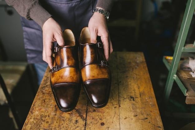 Schuhmacher in der werkstatt, die schöne lederschuhe herstellt.