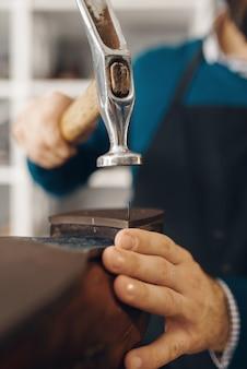 Schuhmacher klopft an die ferse des schuhs, schuhreparaturservice. handwerkskunst, schuhmacherwerkstatt, meisterarbeiten mit stiefeln, schusterjob