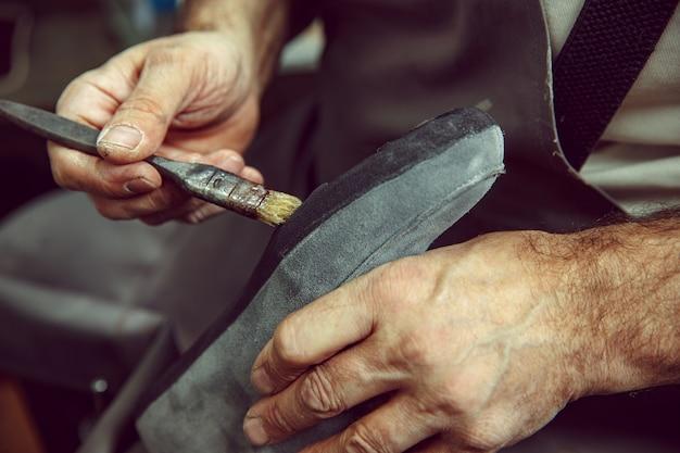 Schuhmacher macht schuhe für männer. er schmiert spezielle flüssigkeit mit einem pinsel. der mann im frauenberuf. konzept der gleichstellung der geschlechter